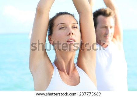 Couple doing yoga and relaxation exercises by the sea - stock photo