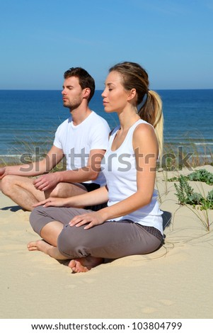 Couple doing yoga exercices on a sandy beach - stock photo