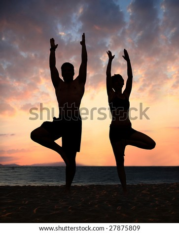 Couple doing yoga exercise on the beach