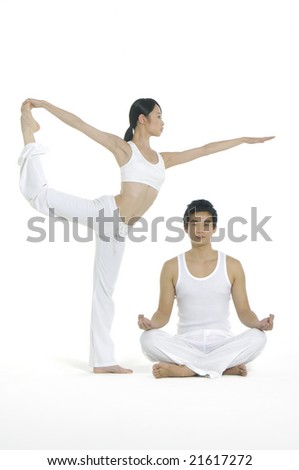 Couple doing yoga exercises together - stock photo