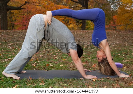 couple doing yoga in the park  - stock photo