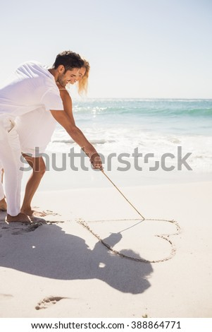 Couple drawing heart on sand on the beach