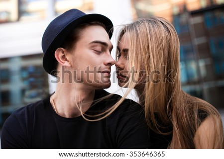 Couple dressed in black looking at each other, the guy wear black hat, a girl flying hair, close-up portrait - stock photo