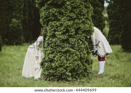 Couple dressed in Victorian style hides behind the green tree
