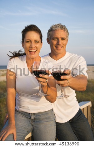 Couple drink red wine on the beach and toast to the camera. Vertical shot.