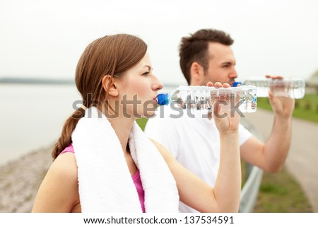 Couple drink water after running - stock photo