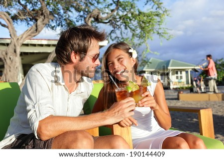 Couple drinking alcohol Mai Tai cocktails at Hawaii beach bar club at sunset. Beautiful asian girl flirting and enjoying alcoholic drinks outside on terrace with caucasian male.  - stock photo