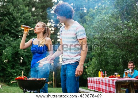 Couple drinking beer and making barbecue together. - stock photo