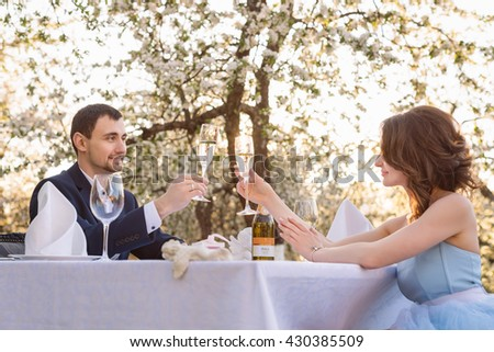 Couple drinking champagne outdoor. Young man making a proposal of marriage. Love, couple, date, wedding concept.