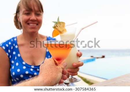 couple drinking cocktail at tropical beach resort - stock photo