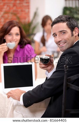 Couple drinking expresso in a cafe with a laptop screen left blank for your image - stock photo