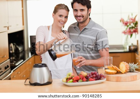 Couple drinking fruits juice in their kitchen