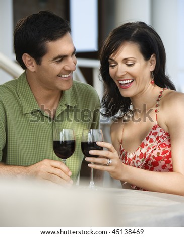 Couple drinking red wine at an outdoor cafe. Vertical shot. - stock photo