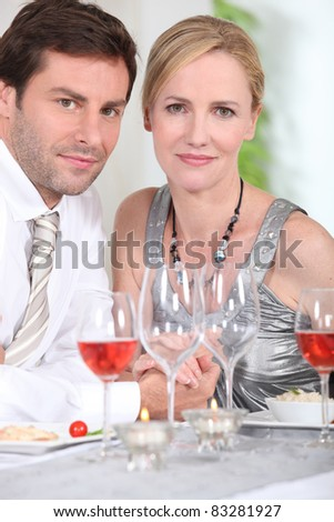 Couple drinking rose wine with dinner - stock photo