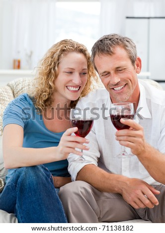 Couple drinking some red wine in the living room at home - stock photo