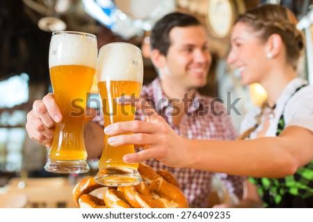 Couple drinking wheat beer in bavarian restaurant - stock photo