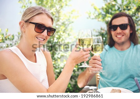 Couple drinking white wine at lunch while on summer vacation - stock photo