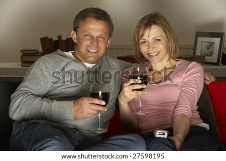 Couple Drinking Wine And Watching Television - stock photo