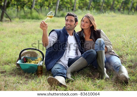 Couple drinking wine in a vineyard - stock photo