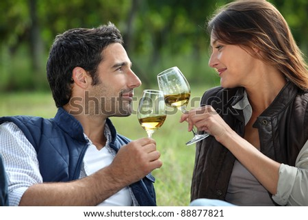Couple drinking wine in field - stock photo