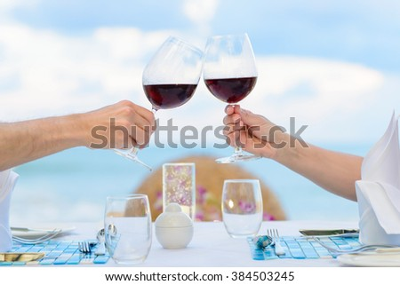 Couple drinking wine in romantic dinner on twilight, closeup. Selective focus, shallow depth of field. - stock photo