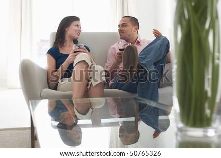 Couple drinking wine, talking on sofa - stock photo