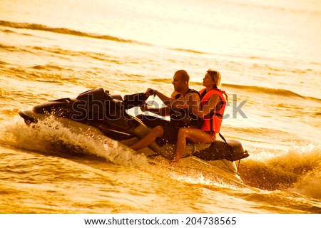 couple drive on the jet ski above the water at sunset .silhouette. spray. - stock photo