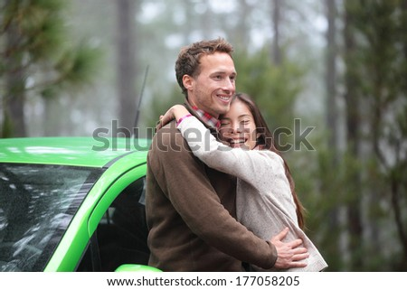 Couple driving in green car in love on travel. Happy drivers in new rental car on vacation holidays road trip resting in forest embracing and hugging in romance outdoors. Asian woman, Caucasian man.