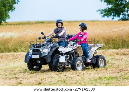 Couple driving off-road with quad bike or ATV - stock photo