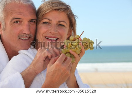 Couple eating a bunch of grapes - stock photo