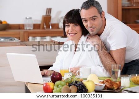 Couple eating breakfast in the kitchen - stock photo