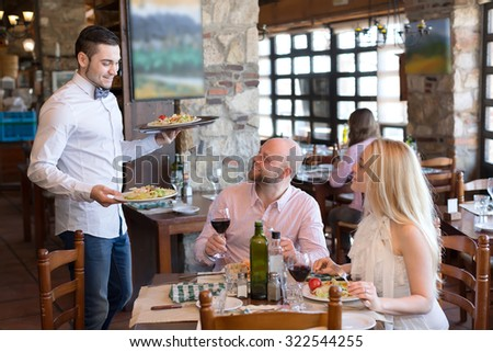 Couple eating delicious and fresh salads in a restaurant while waiter brings them more vegetarian food