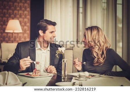 Couple eating dessert in a restaurant  - stock photo