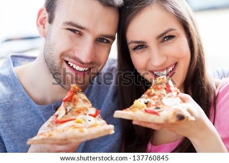 Couple eating pizza - stock photo