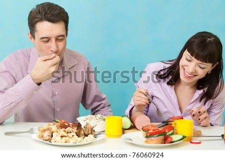 Couple eating salad on kitchen - stock photo
