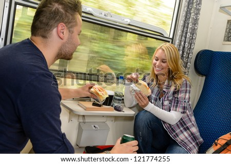 Couple eating sandwiches on train traveling smile vacation hungry lunch - stock photo