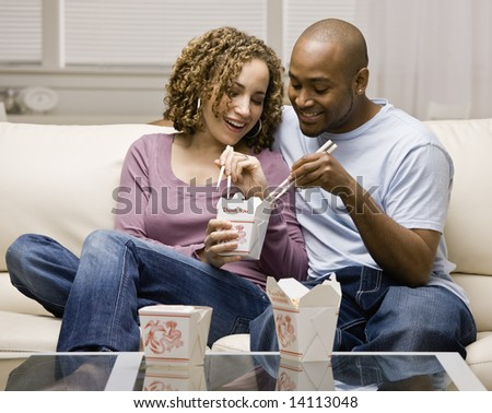 Couple eating take-out Chinese food - stock photo