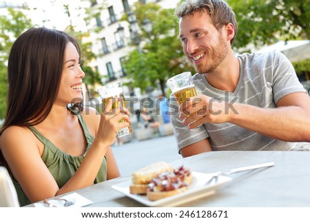 Couple eating tapas drinking beer in Madrid, Spain. Romantic man and woman enjoying local traditional food on square in Madrid. Asian woman and Caucasian man dating. - stock photo