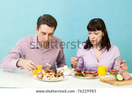 Couple eats vegetables and salad on kitchen - stock photo