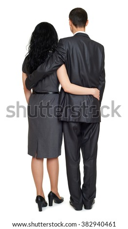 Couple embrace backside, rear view, studio portrait on white. Dressed in black suit. - stock photo