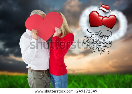 Couple embracing and holding heart over faces against green grass under blue and orange sky - stock photo
