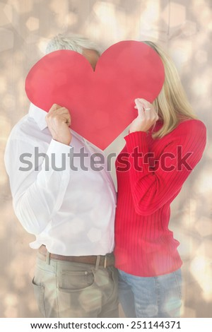 Couple embracing and holding heart over faces against light glowing dots design pattern - stock photo