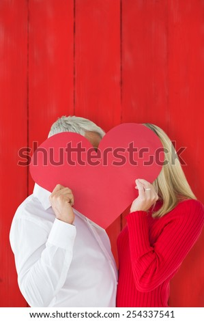 Couple embracing and holding heart over faces against red wooden planks - stock photo