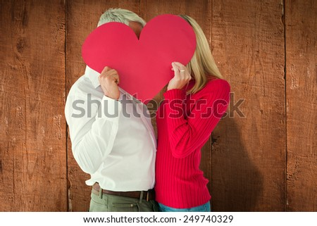 Couple embracing and holding heart over faces against wooden planks - stock photo