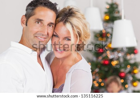 Couple embracing at christmas by dinner table - stock photo