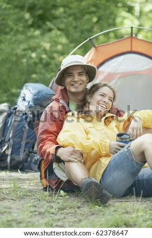 Couple embracing at their campsite - stock photo