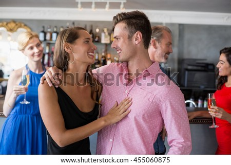 Couple embracing each other in restaurant and friends standing in background - stock photo