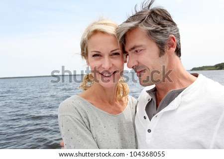 Couple embracing each other on a bridge by a lake - stock photo