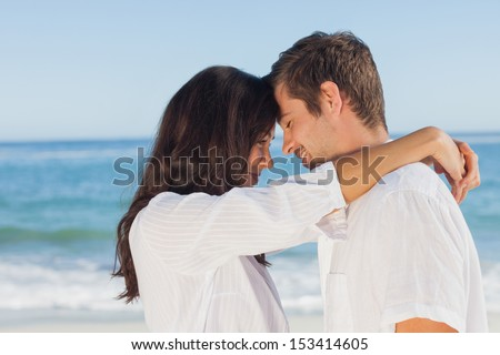 Couple embracing each other on the beach against ocean on sunny day - stock photo