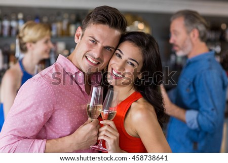 Couple embracing each other while having wine in restaurant
